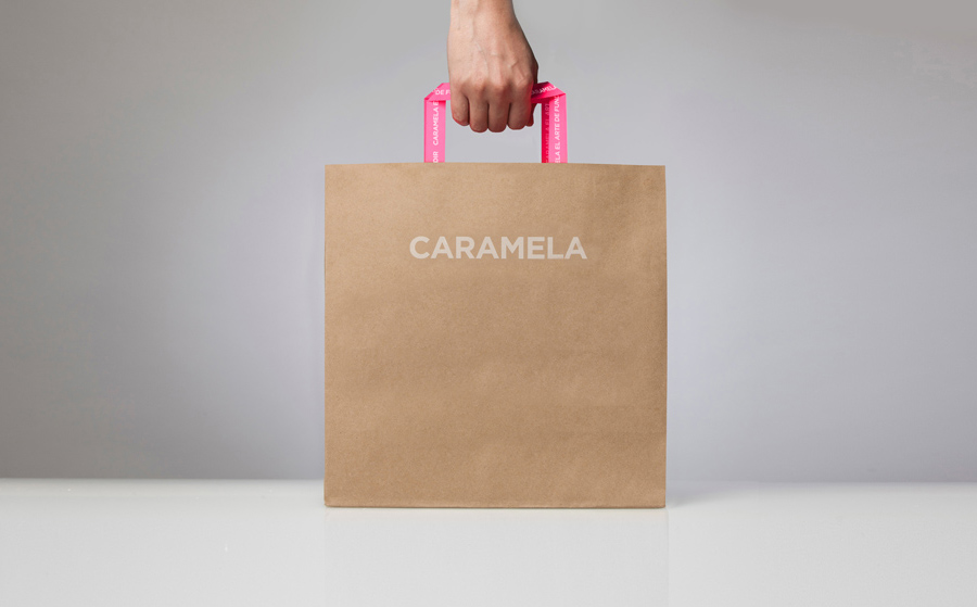 Packaging with pink neon stickers across an unbleached substrate designed by Anagrama for chocolate boutique and caterer Caramela