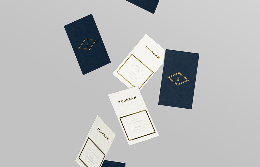 Logotype and business card with gold foil detail for British multinational venture capital firm Tourean designed by Anagrama