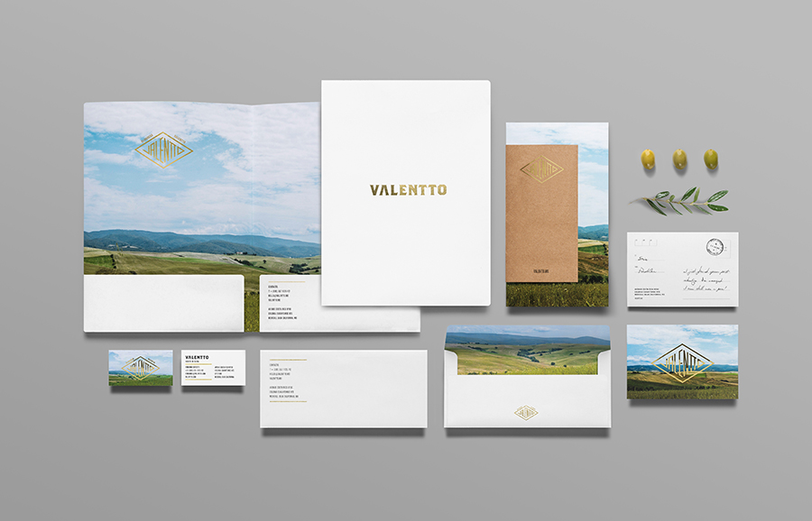 Logo and stationery set with gold foil and photographic landscape detail designed by Anagrama for olive oil brand Valentto