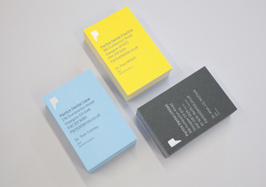 Logo and business cards with yellow blue and grey board detail designed by Freytag Anderson for Partick Dental featured on BPO