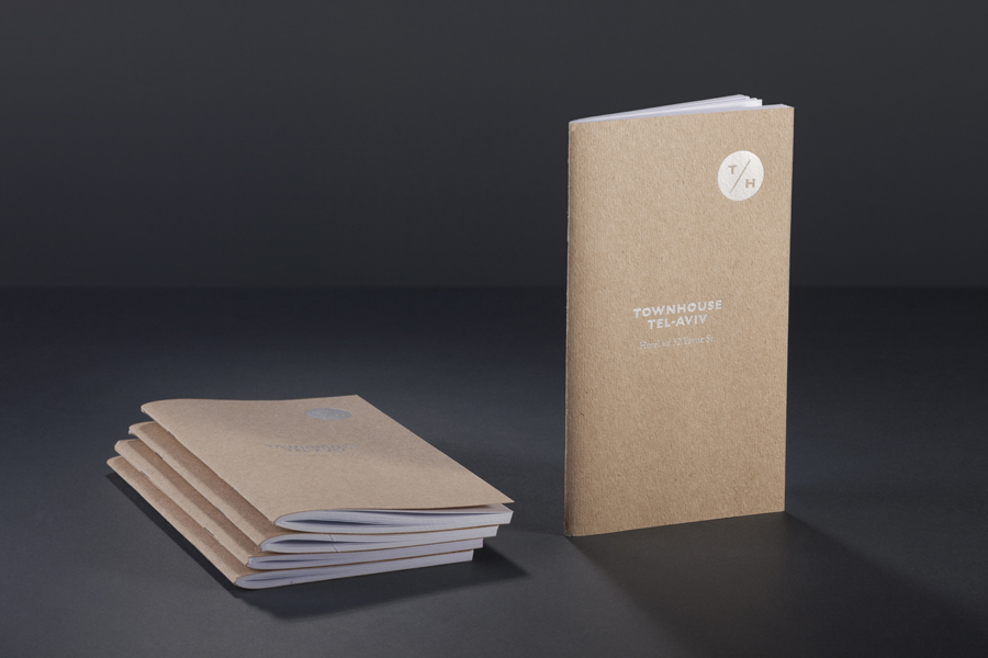 Logo and notebook with white ink detail across an unbleached paper for Tel Aviv hotel Townhouse designed by Koniak