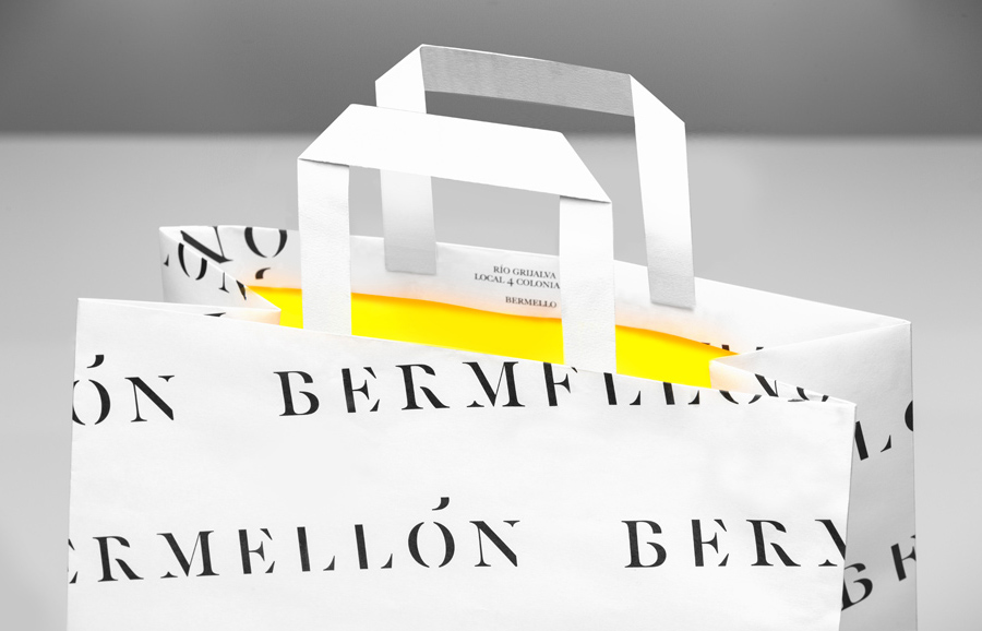 Paper bag with white exterior and bright yellow interior for confectionery shop Bermellón designed by Anagrama