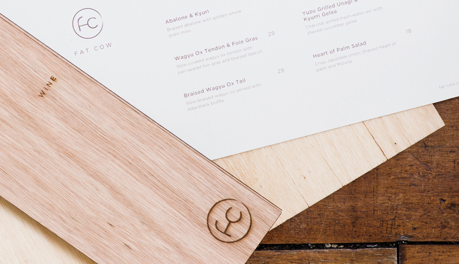 Logo and wood menu covers with heat treated detail for specialist beef restaurant Fat Cow designed by Foreign Policy