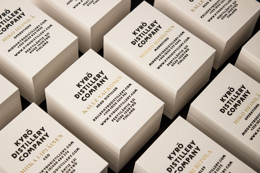 Business cards with laid paper and gold foil detail designed by Werklig for Kyrö Distillery Company