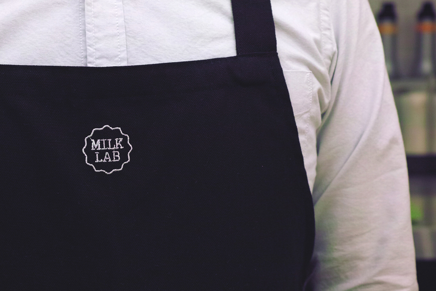 Milk Lab pinny with stitched logo detail designed by Studio FNT