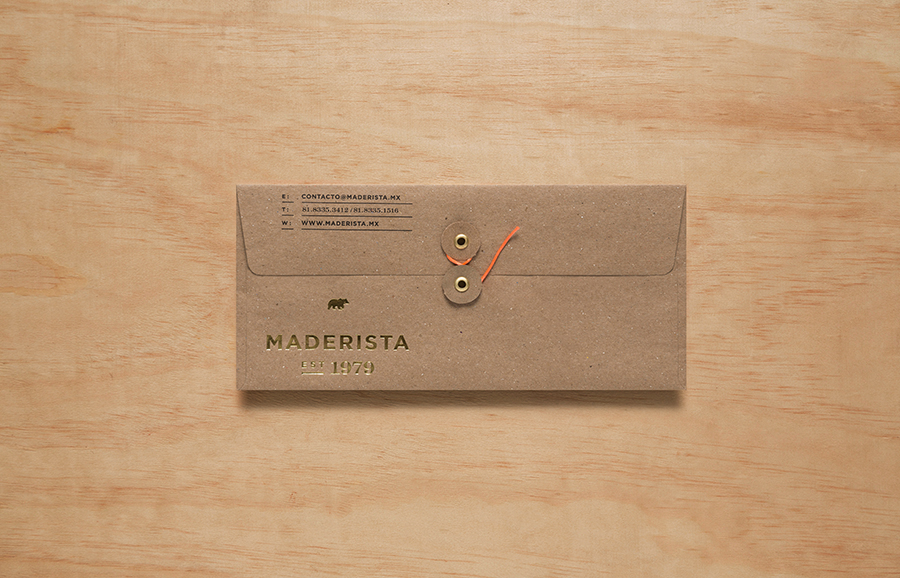 Logo and envelope with gold foil finish across an unbleached substrate designed by Anagrama for San Pedro-based carpentry studio Maderista