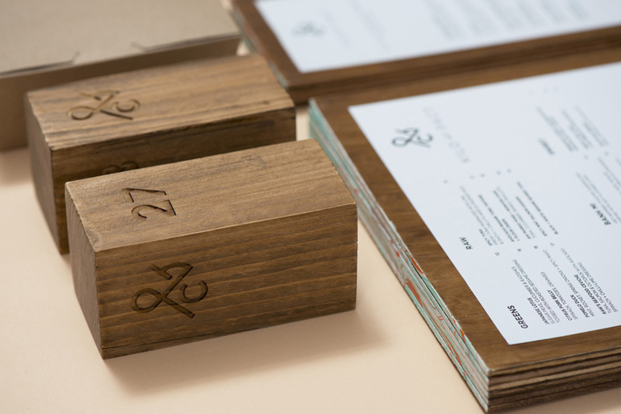 Logo, wood carved table numbers and wood veneer menus designed by Acre for co-branded retail partnership Pact