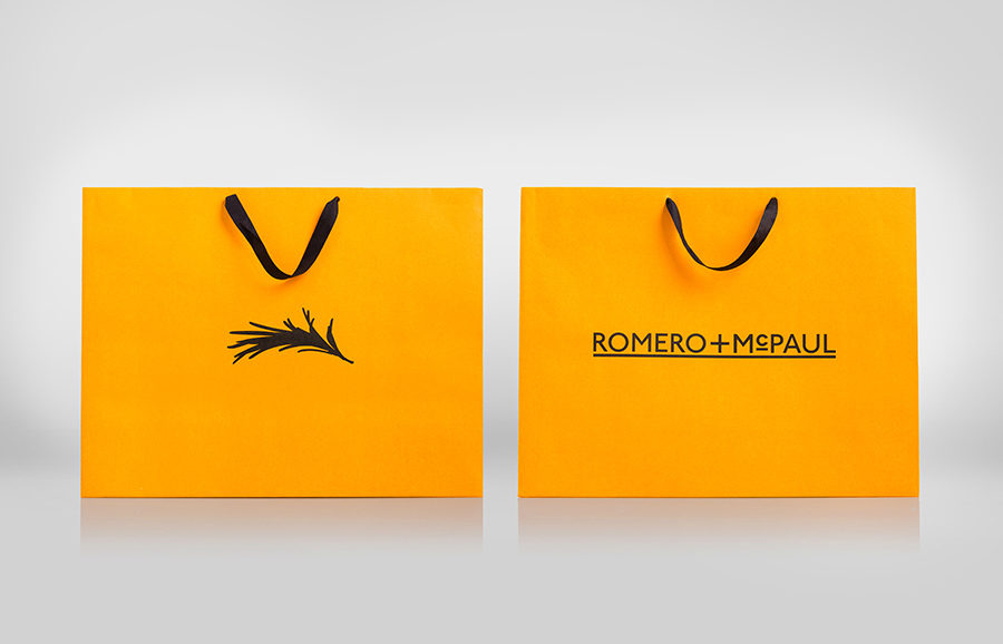 Logo and orange shopping bags created by Anagrama for luxury slipper brand Romero+McPaul