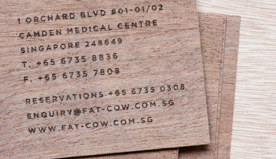 Logo and wood veneer business card with heat treated detail for specialist beef restaurant Fat Cow designed by Foreign Policy