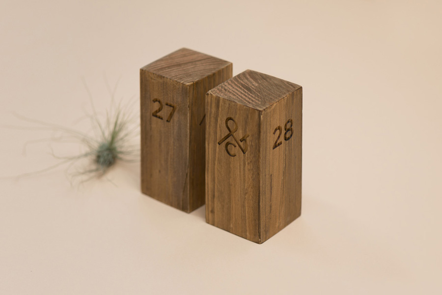 Logo, wood carved table numbers designed by Acre for co-branded retail partnership Pact
