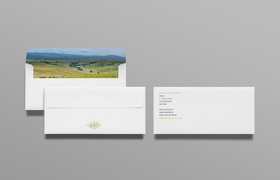 Logo and envelope with gold foil and photographic landscape detail designed by Anagrama for olive oil brand Valentto
