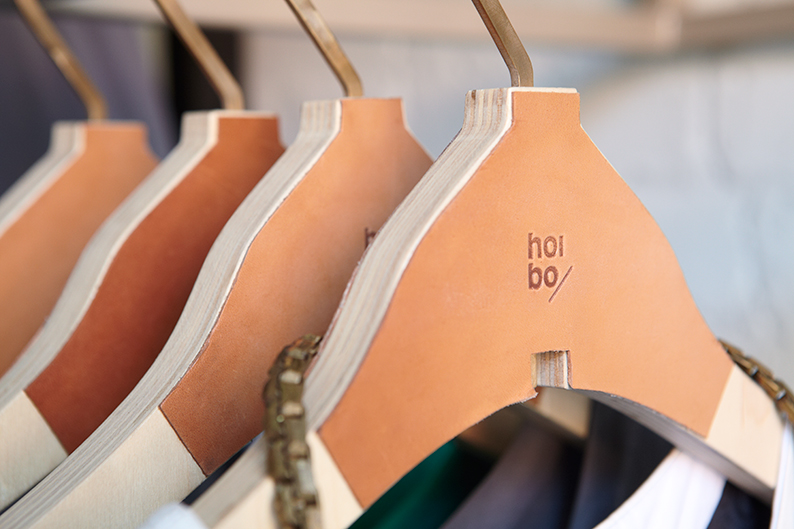 Logo and hanger with leather panel detail designed by Blok for luxury bag, clothing and accessories brand Hoi Bo