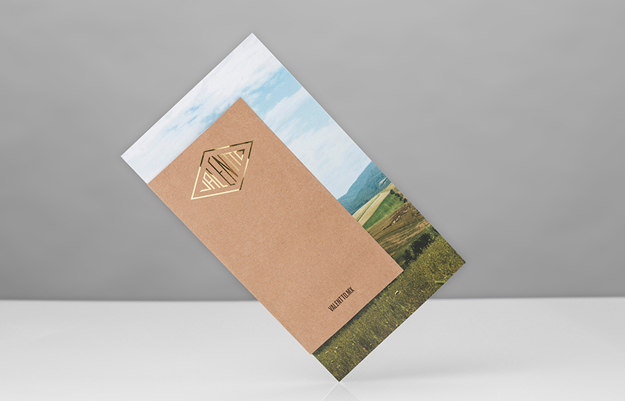 Logo and pamphlet with gold foil, photographic landscape and unbleached material detail designed by Anagrama for olive oil brand Valentto