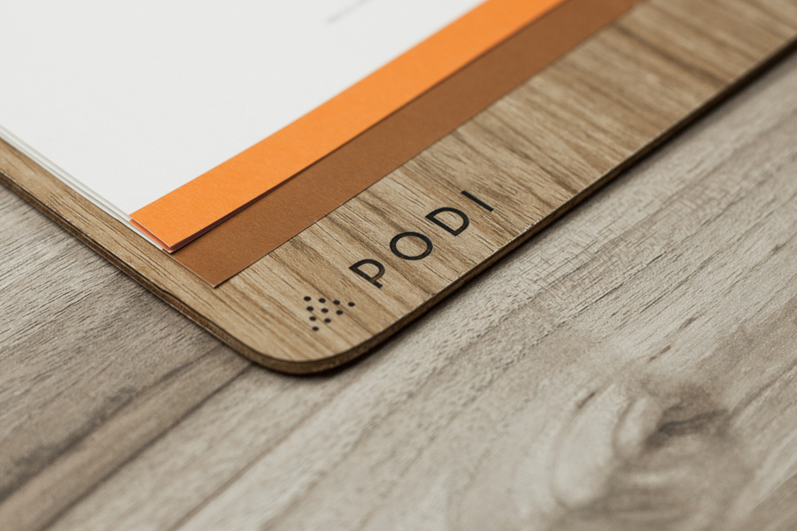 Logotype, menu with wood detail and coasters designed by Bravo Company for Singapore-based organic restaurant Podi
