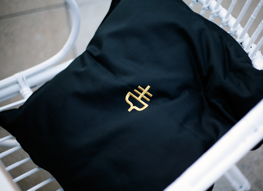 Cushion with gold stitched logo detail designed by Graphical House for The Empire Café
