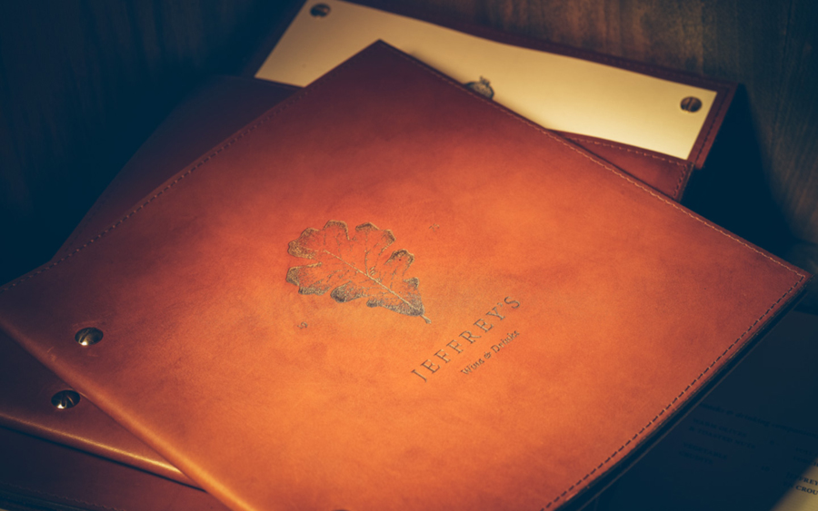 Leather bound menu with stippled botanical illustration by FÖDA Studio for Jeffrey's