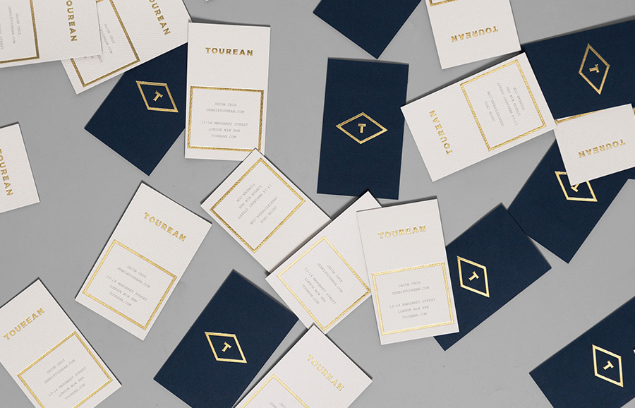 Logotype and business with card gold foil detail for British multinational venture capital firm Tourean designed by Anagrama