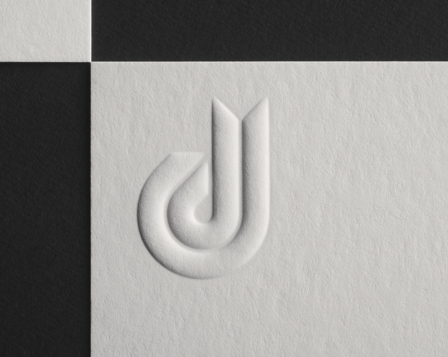 Logo and blind embossed business card detail for Daniel Juncadella designed by Mucho