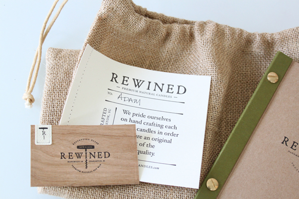 Logo, canvass bag and wood veneer and unbleached paper business card for candle in a wine bottle brand Rewined designed by Stitch