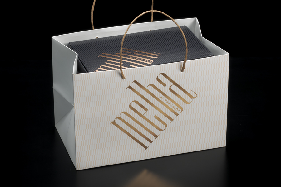 Visual identity and copper foiled pâtisserie packaging designed by Pentagram for London cafe Melba at The Savoy