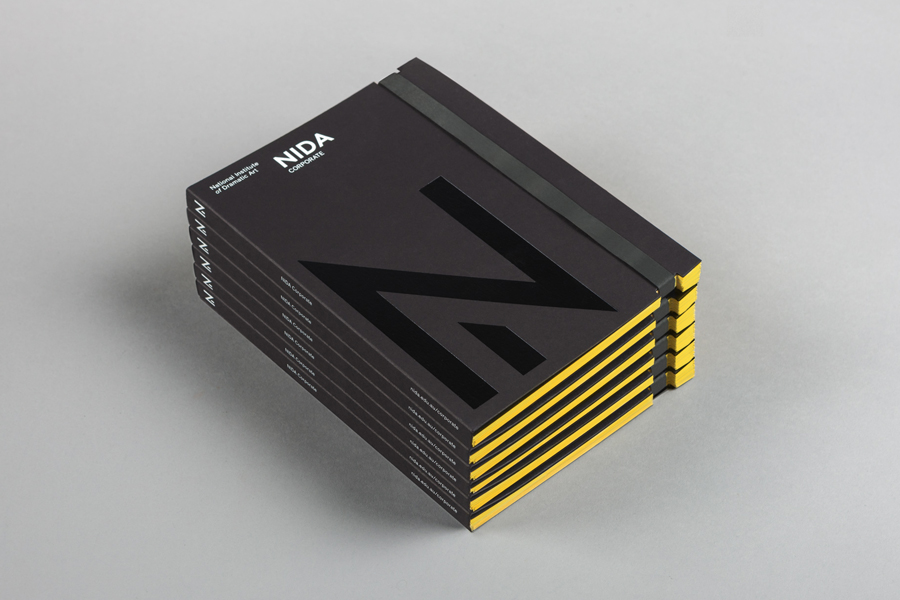 Black block foiled corporate handbook designed by Maud for The National Insti­tute of Dra­matic Art