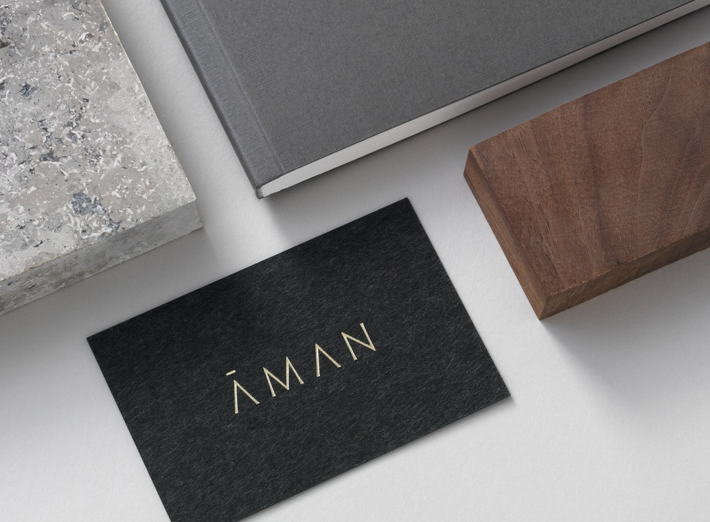 Black board and gold block foiled business card for luxury resort company Aman designed by Construct