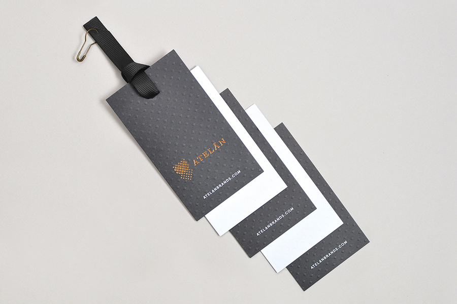 Tags with copper foil and blind emboss detail for Latin American fashion brand champion Atelán by Firmalt