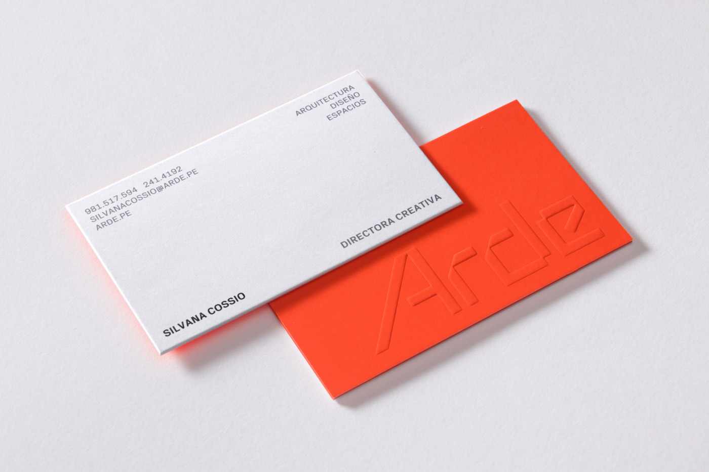 Business cards for Peruvian architecture business Arde by IS Creative Studio. These feature a bright fluorescent orange ink and blind emboss print print finish.