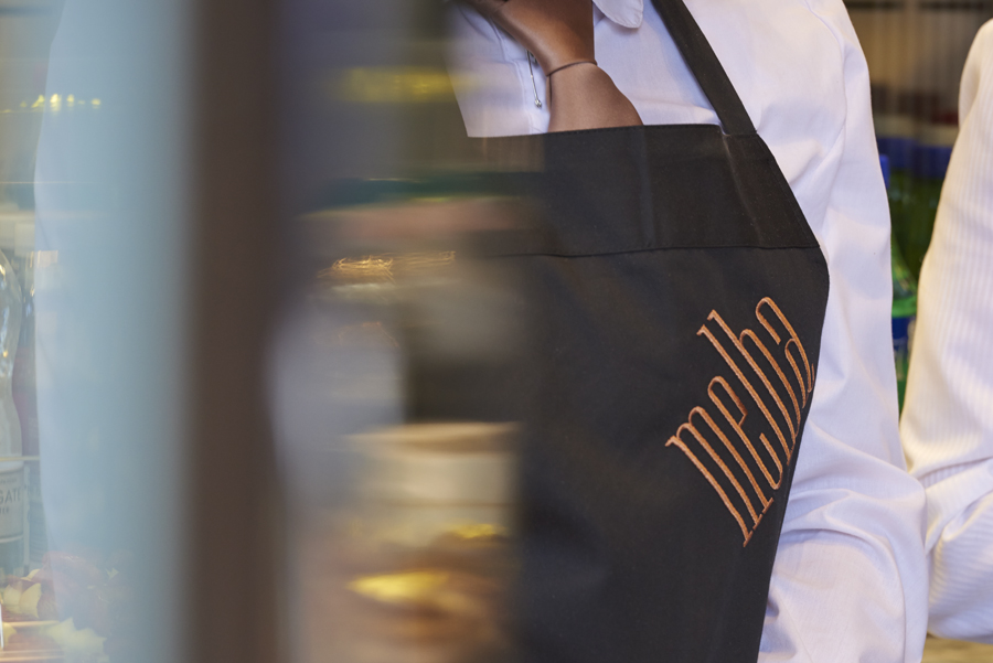 Embroidered and branded apron designed by Pentagram for London patisserie and cafe Melba at The Savoy