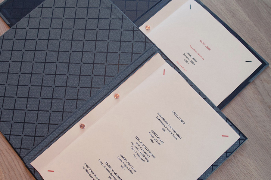 Fabric menu with salmon coloured paper detail for Norwegian brasserie Festningen designed by Uniform