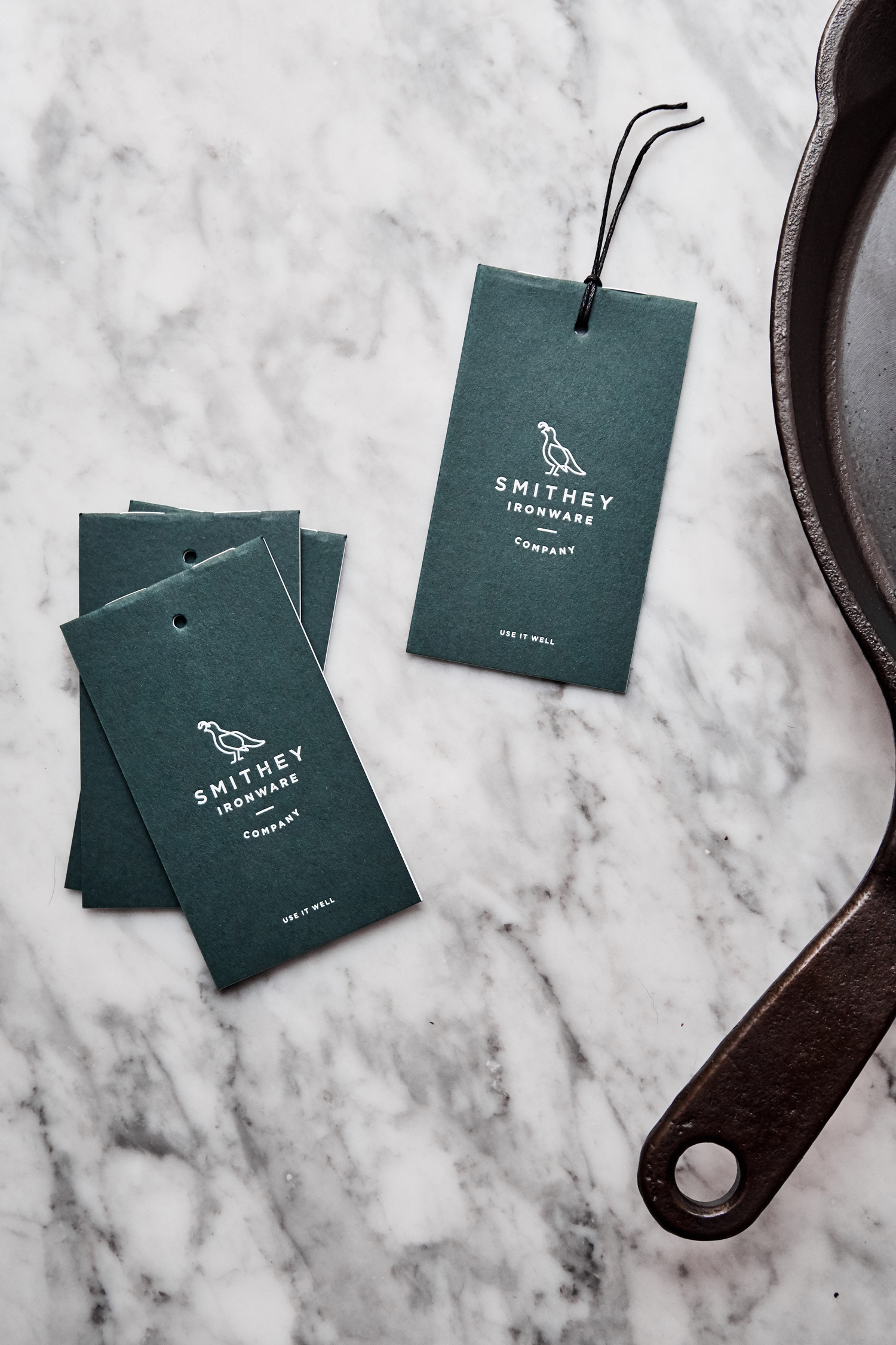 Brand identity and tags with green paper and white ink detail for Smithey Ironware Company by Charleston based Stitch, United States
