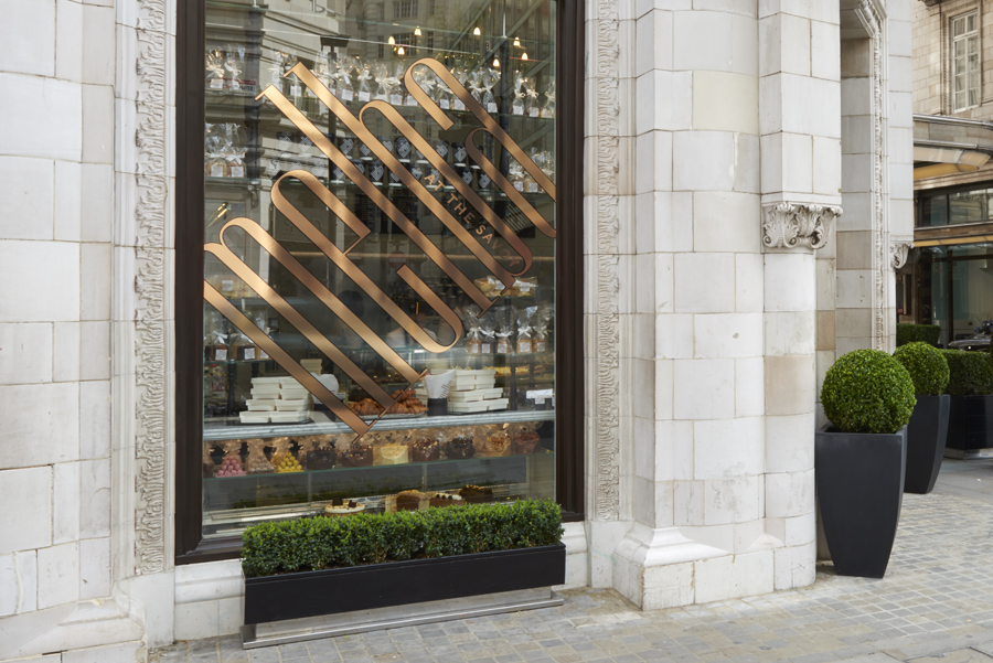 Logotype as a copper window detail designed by Pentagram for London patisserie and cafe Melba at The Savoy